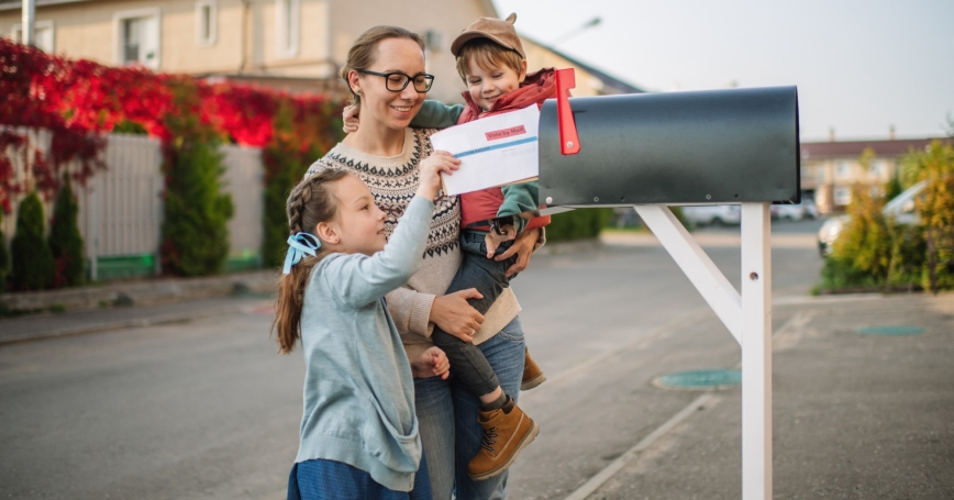 Woman and two young children place a ballot in a mailbox, photo by ArtMarie/Getty Images