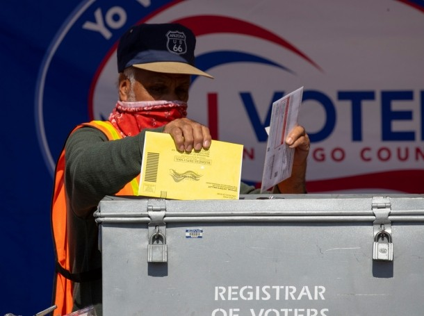 An election worker places mail-in ballots into a voting box at a drive-through drop off location in San Diego, California, October 19, 2020, photo by Mike Blake/Reuters