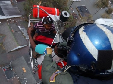Petty Officer 1st Class Steven Huerta hoists two children from their rooftop into a Coast Guard rescue helicopter after flooding caused by Hurricane Katrina in New Orleans, LA, August 29, 2005, photo by Senior Chief Petty Officer Kyle Niemi/U.S. Coast Guard