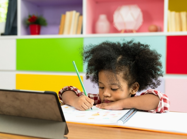 Young child sitting in front of a tablet computer writing in a notebook, photo by Sushiman/Getty Images