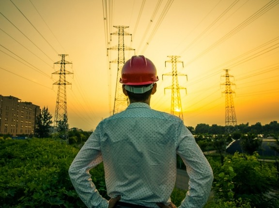 Man wearing a hard hat facing away looking at electricity pylons and wires, photo by xijian/Getty Images