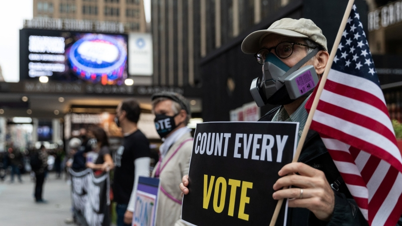 A man wearing a protective mask due to COVID-19 pandemic holds a sign outside Madison Square Garden, which is used as a polling station, on the first day of early voting in Manhattan, New York, October 24, 2020, photo by Jeenah Moon/Reuters