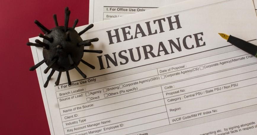Health insurance form with model of COVID-19 virus and pen, photo by ajaykampani/Getty Images