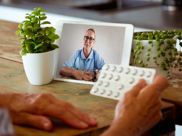 Senior woman using digital tablet and having video call with nurse, photo by izusek/Getty Images