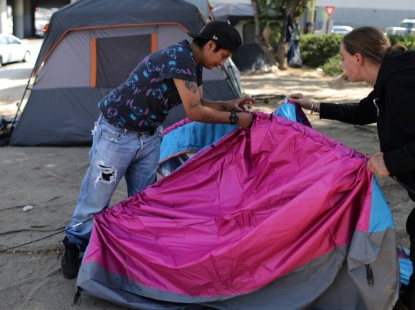 Christina Bojorquez and Kimberly Decoursey pitch a tent in their encampment next to a freeway in Los Angeles, California, October 14, 2019, photo by Lucy Nicholson/Reuters