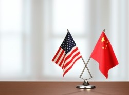 U.S. and China flags crossed on a table, photo by studiocasper/Getty Images