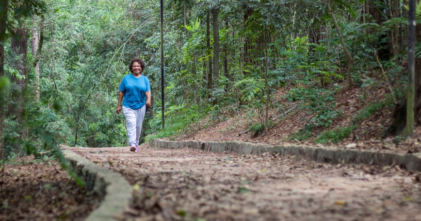 Older woman wakling on a trail in the woods, photo by Maurian Soares Salvador/Getty Images