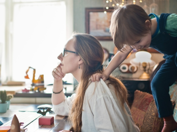 Woman working from home with young son, photo by ArtMarie/Getty Images