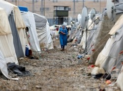 A Syrian refugee woman walks between tents in Nizip refugee camp, near the Turkish-Syrian border in Gaziantep province, Turkey, November 30, 2016, photo by Umit Bektas/Reuters