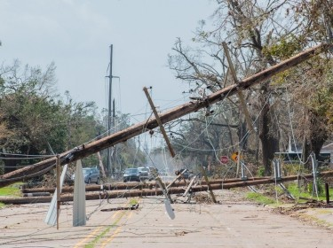 Telephone poles toppled over after Hurricane Laura, photo by Leslie Scarbrough/Getty Images