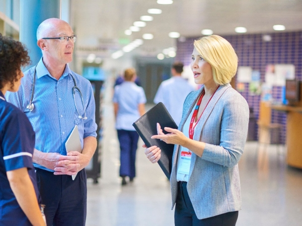 Hospital administrator and medical staff in a hospital hallway, photo by sturti/Getty Images