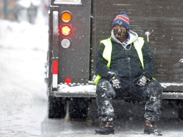 A worker sits on the back of a delivery truck during a snow storm in Boston, Massachusetts, December 17, 2020, photo by Brian Snyder/Reuters