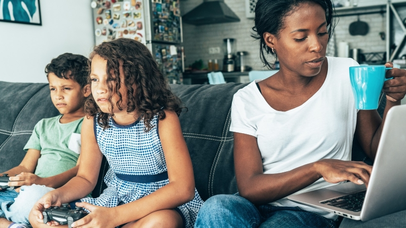 Woman works at home while her children play video games, photo by filadendron/Getty Images