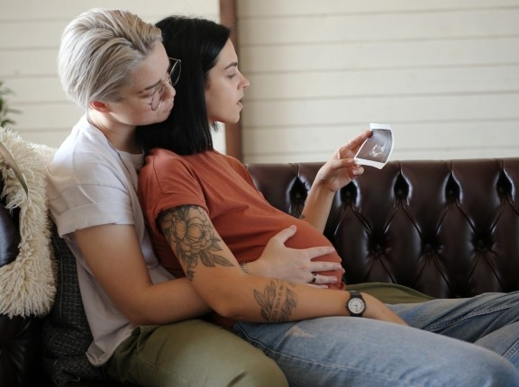 Lesbian couple view ultrasound of their baby, photo by Teraphim/Getty Images