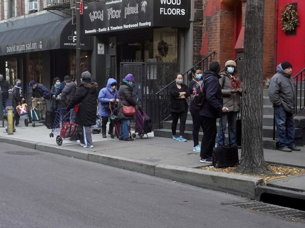 People wait in line at the St. Clements Food Pantry in New York City, December 11, 2020, poto by Carlo Allegri/Reuters