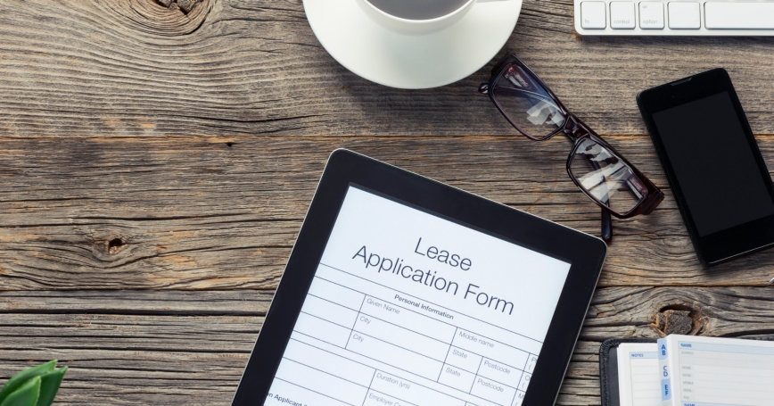 Lease application form on a tablet with glasses, keyboard, and coffee cup, photo by courtneyk/Getty Images