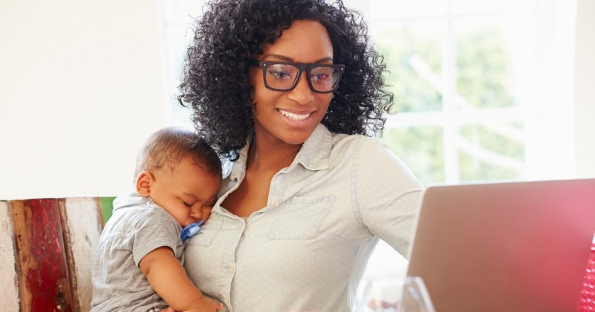 Mother working on a laptop while holding her  baby, photo by monkeybusinessimages/Getty Images