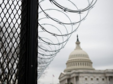 The U.S. Capitol behind security fencing in Washington, D.C., January 25, 2021, photo by Graeme Sloan/Sipa USA/Reuters