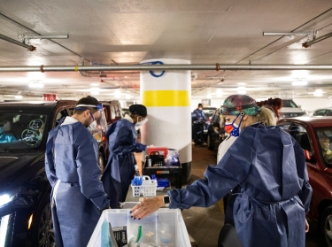 Nurses prepare to vaccinate people at a drive-through COVID-19 vaccination site in Detroit, Michigan, January 15, 2021, photo by Emily Elconin/Reuters
