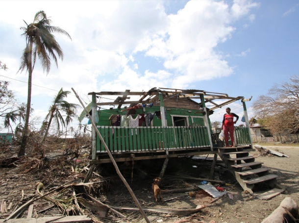 A woman stands on a ruined building after Hurricane Eta, in Wawa Bar, a Miskito indigenous community in Puerto Cabezas, Nicaragua, November 23, 2020, photo by Katlyn Holland/CRS /Latin America News Agency/Reuters