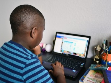 Nine year old student Jordan in his bedroom attending online school in Broward County, Florida, March 31, 2020, photo by Johnny Louis/Reuters