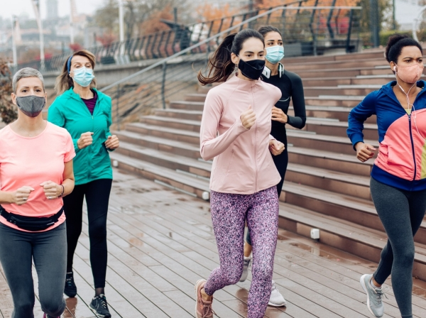 Group of women wearing face masks while running in the city during rainy and gloomy weather, photo by RgStudio/Getty Images