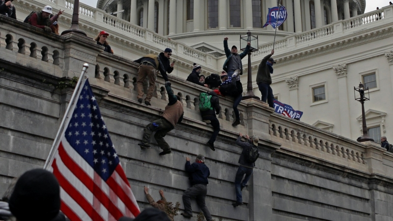 Supporters of the outgoing president, Donald Trump, climb a wall during a deadly mob assault on the U.S. Capitol Building in Washington, D.C., January 6, 2021, January 6, 2021, photo by Jim Urquhart/Reuters