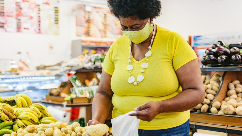 Woman in the grocery store buying produce, photo by Igor Alecsander/Getty Images