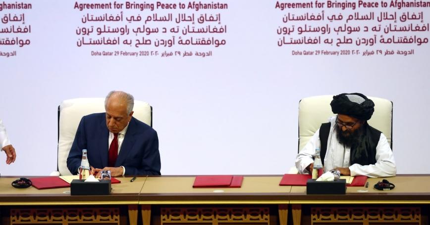 Mullah Abdul Ghani Baradar, the leader of the Taliban delegation, signs an agreement with Zalmay Khalilzad, U.S. envoy for peace in Afghanistan in Doha, Qatar, February 29, 2020, photo by Ibraheem al Omari/Reuters