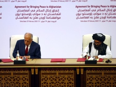 Mullah Abdul Ghani Baradar, the leader of the Taliban delegation, signs an agreement with Zalmay Khalilzad, U.S. envoy for peace in Afghanistan in Doha, Qatar, February 29, 2020, photo by Ibraheem al Omari/Reuters