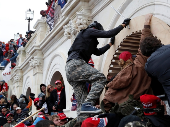 Supporters of Donald Trump scale a wall as they storm the U.S. Capitol, in Washington, DC, January 6, 2021, photo by Shannon Stapleton/Reuters