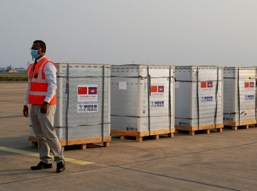 A worker stands next to the shipment of 600,000 doses COVID-19 vaccines donated by China at the Phnom Penh International Airport, in Phnom Penh, Cambodia, February 7, 2021, photo by Cindy Liu/Reuters
