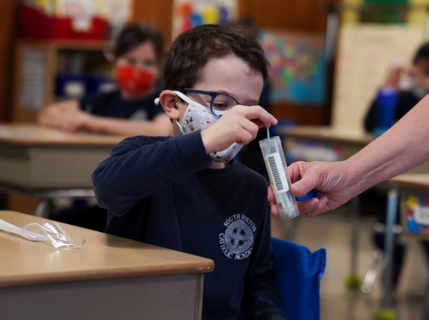 A child places his COVID-19 testing swab in a vial at South Boston Catholic Academy in Boston, Massachusetts, January 28, 2021, photo by Allison Dinner/Reuters