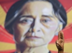 A person shows the three-finger. salute in front of a placard with the image of Aung San Suu Kyi during a protest against the military coup in Yangon, Myanmar, February 15, 2021, photo by Stringer/Reuters