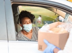 A woman receives a box of donated food items during the COVID-19 pandemic in her car, photo by SDI Productions/Getty Images