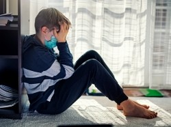 Boy sitting by the window, wearing surgical mask with his head in his hands, photo by Imgorthand/Getty Images