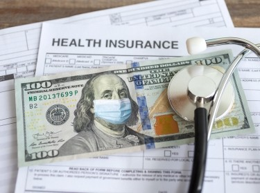 Stethoscope and U.S. one hundred dollar bill with face mask on insurance form, photo by aldarinho/Getty Images