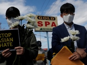 Men hold flowers during a vigil at a makeshift memorial outside the Gold Spa following the deadly shootings in Atlanta, Georgia, March 21, 2021, photo by Shannon Stapleton/Reuters