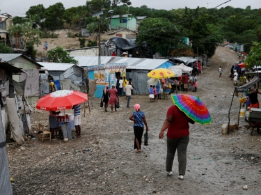 People walk down the street at a camp for displaced people while Hurricane Matthew approaches in Port-au-Prince, Haiti, October 3, 2016, photo by Carlos Garcia Rawlins/Reuters
