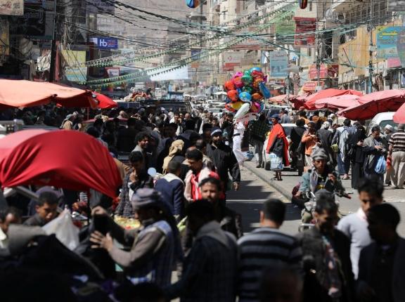 People walk at a street market in Sanaa, Yemen, February 5, 2021, photo by Khaled Abdullah/Reuters