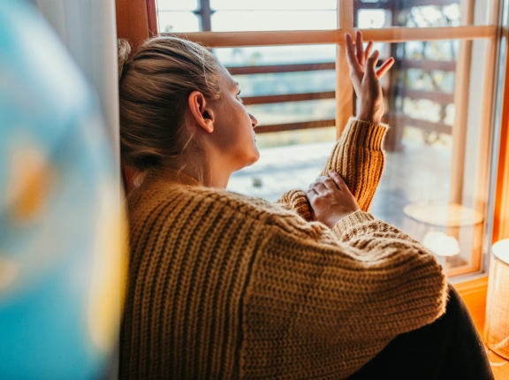 Woman sitting beside window at home, photo by SimonSkafar/Getty Images