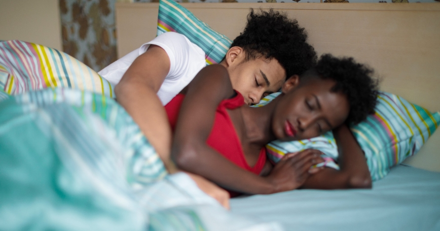 Young Black couple asleep in bed, photo by Eva-Katalin/Getty Images