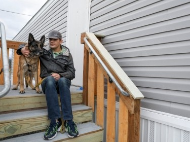 After losing their home to wildfires, Nick Schumacher and his dog Charlie prepare to move into a FEMA trailer in Mill City, Oregon, January 29, 2021, photo by Abigail Dollins/Statesman Journal via Reuters