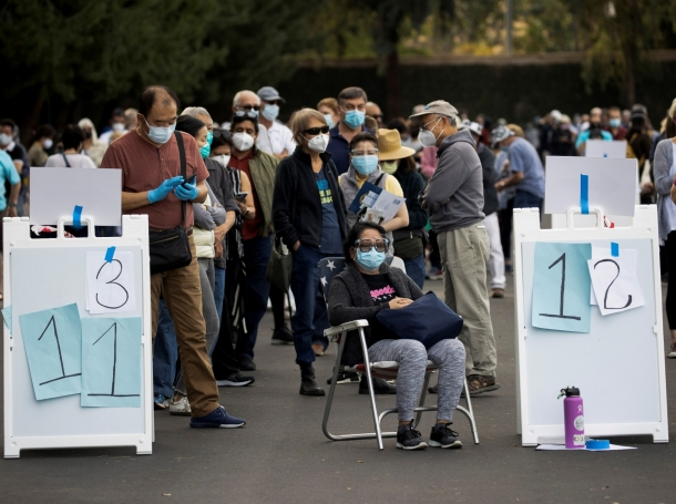 People wait in line in a Disneyland parking lot to receive the COVID-19 vaccine at a mass vaccination site in Anaheim, California, January 13, 2021, photo by Mario Anzuoni/Reuters