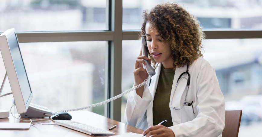 A doctor calls a patient using a landline, photo by SDI Productions/Getty Images