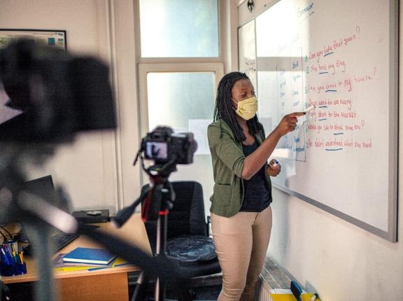 Teacher standing at whiteboard teaching remotely, photo by Viktorcvetkovic/Getty Images