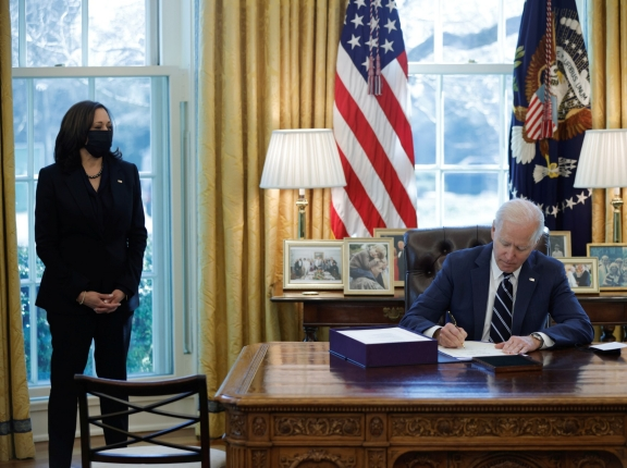 President Joe Biden signs the American Rescue Plan with Vice President Kamala Harris looking on, in the Oval Office at the White House in Washington, D.C., March 11, 2021, photo by Tom Brenner/Reuters