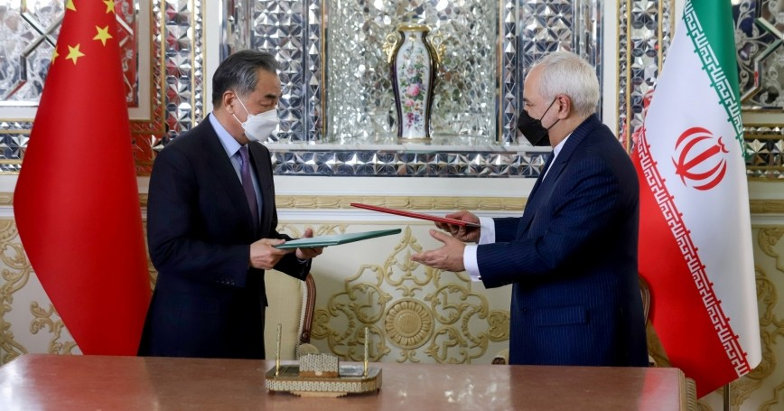 China's Foreign Minister Wang Yi and Iran's Foreign Minister Mohammad Javad Zarif exchange documents during the signing ceremony of a 25-year cooperation agreement, in Tehran, Iran March 27, 2021, photo by Majid Asgaripour/WANA via Reuters