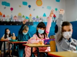 Elementary schoolchildren wearing face masks in a classroom, photo by kevajefimija/Getty Images