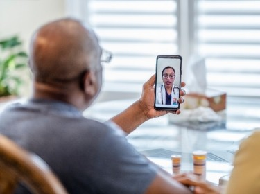 Older couple using a mobile phone for a telemedicine appointment, photo by FatCamera/Getty Images